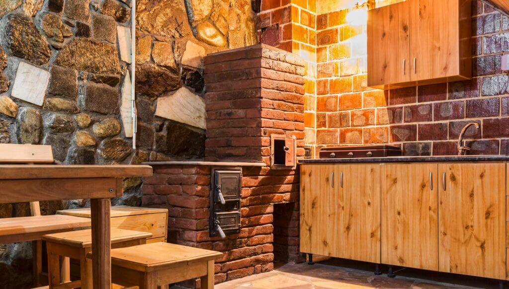 מטבח כפרי עם ציפוי אבן ותנור לבנים